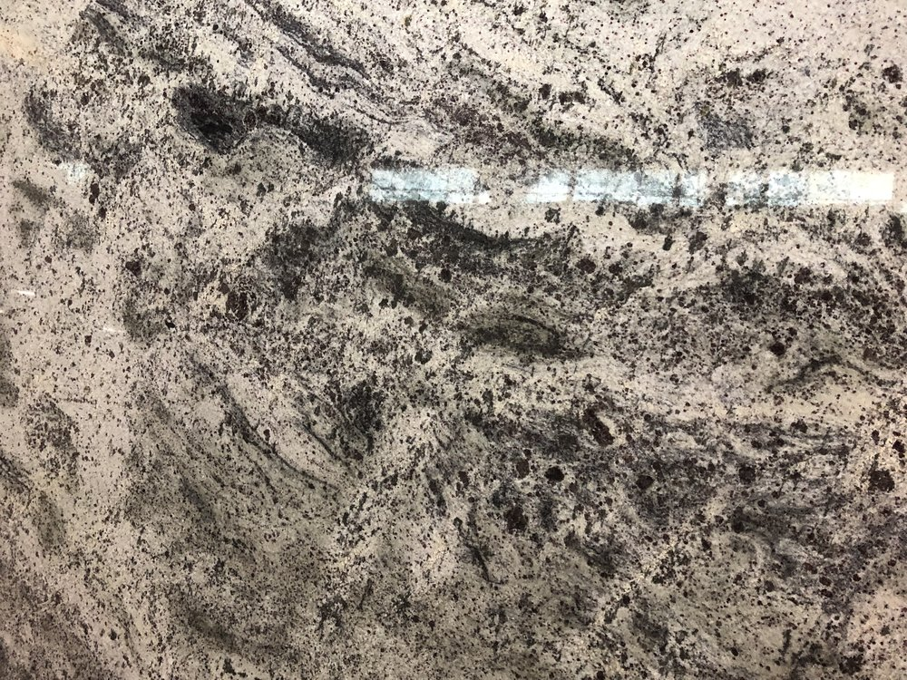 Bianco Gray - Quarried: IndiaMaterial Type: GraniteDescription: predominant grey background with white, green and grey variations with a swirling cloud movement and specks of garnet throughout.