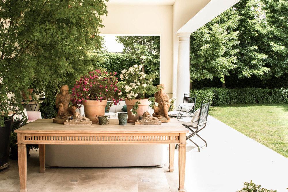Mesa de madera en porche exterior con flores y decoración