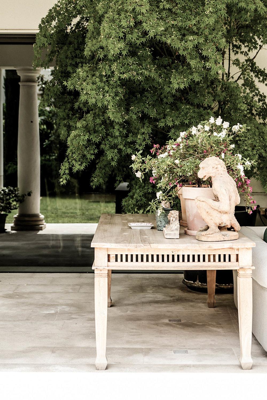 Escultura de mono sobre mesa madera en porche