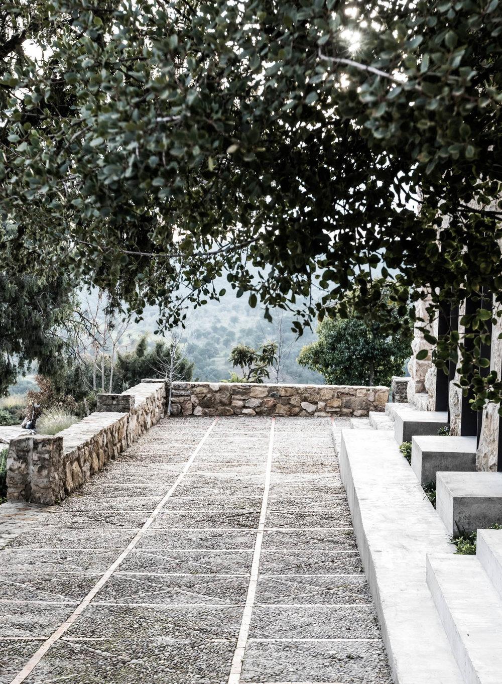 Porche con piedras y paisajismo de Locus