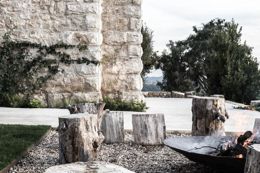 Jardín con troncos y zona de hoguera diseñada por Locus Landscape Architecture