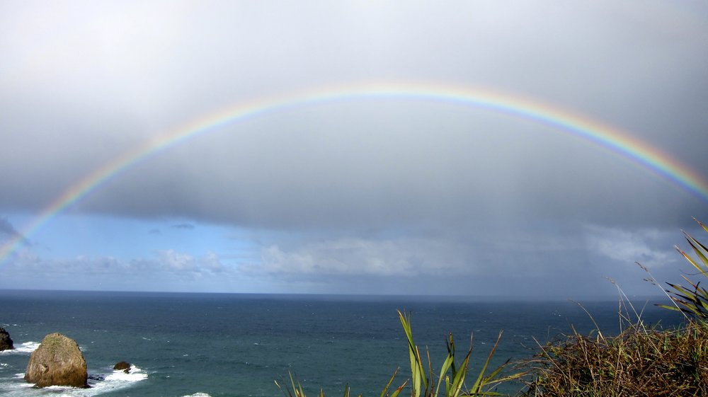Full rainbow over Nugget Point Lighthouse.