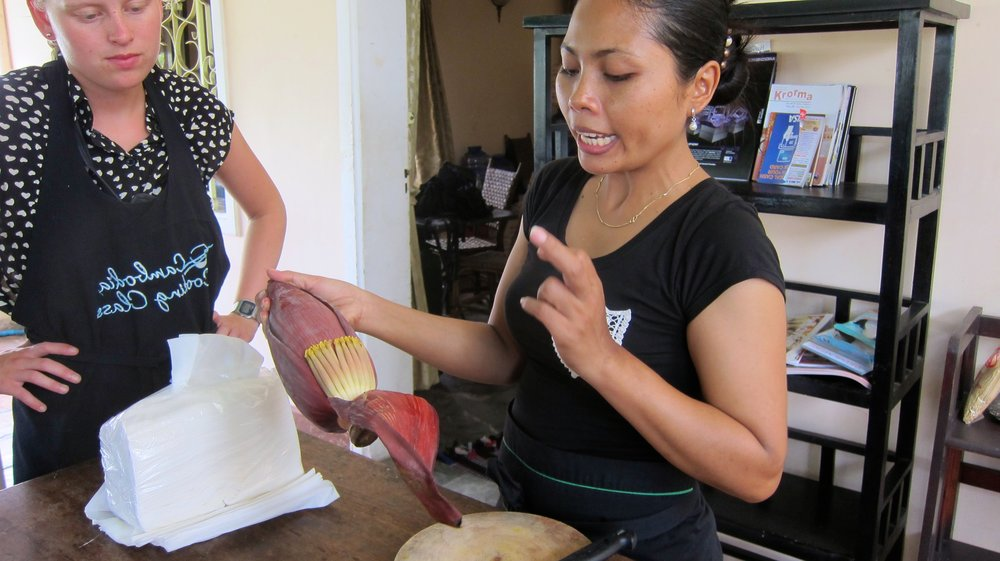 Demonstrating how to peel a banana flower.