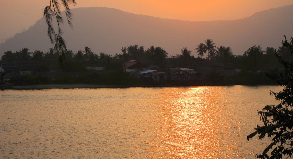 The sun setting over the Mekong River and distant mountains.