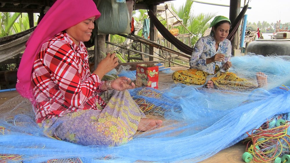 Women making fishing nets for their village's boats.