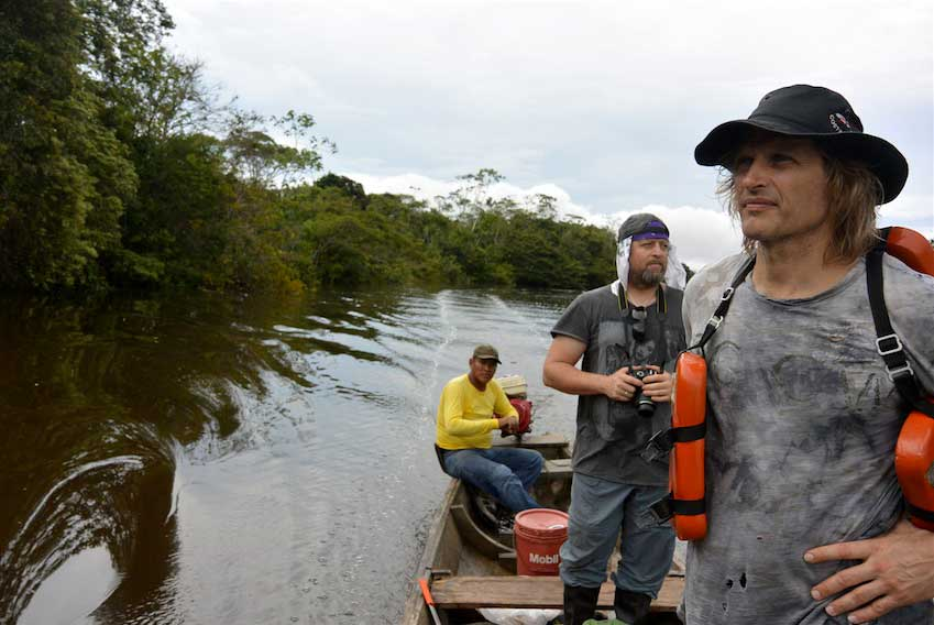 Blackwater tributary of the Amazon Loreto, Peru – Joe and Jake survey the surrounding vegetation as they move slowly down a black water tributary of the Amazon. Identifying rare fruits along the way is a matter of having a sharp trained eye and an ability to discern what you are looking for.