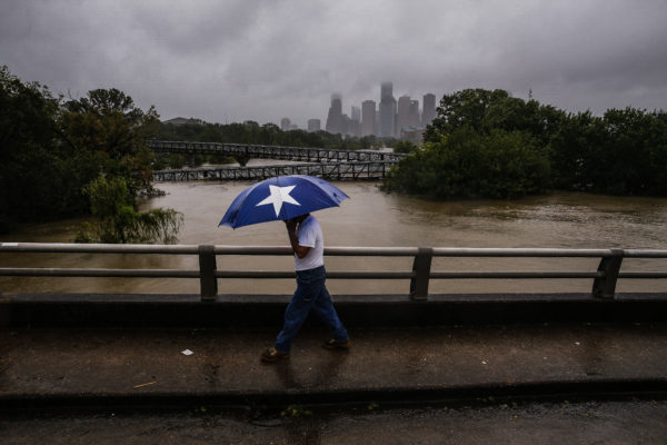 Armando Bustamante walks along Studemont Street over Buffalo Bayou as flood waters from Hurricane Harvey flow toward downtown Houston on Tuesday, Aug. 29, 2017. Michael Ciago/Houston Chronicle