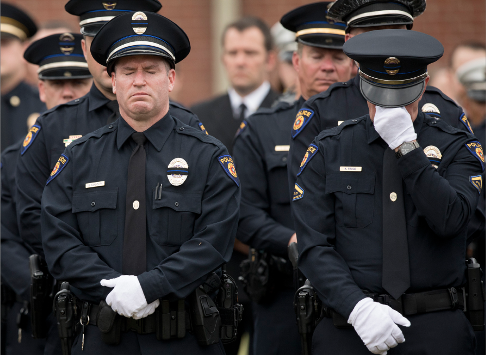 Round Rock police officers Sean Randolph, left, and Kevin Fruge cry at the funeral for Round Rock police officer Charles Whites at Shoreline Church on Wednesday May 2, 2018. Whites, a 19-year veteran of the Round Rock Police Department, died from injuries sustained on February 25 when he was struck by a car while directing traffic around an accident on Interstate 35. [JAY JANNER/AMERICAN-STATESMAN]