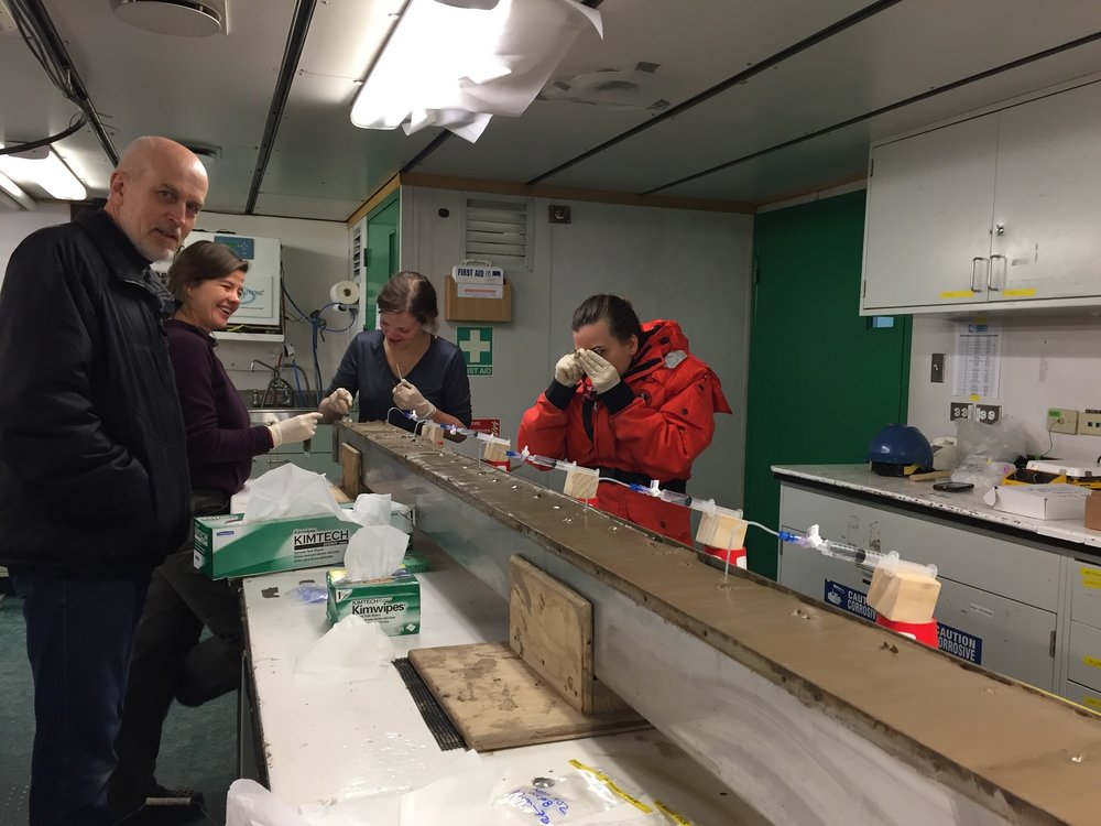 Becky Minzoni looks at the sediments with a hand lens as she describes the grainsize of the core. Also pictured (l to R) THOR PI Rob Larter, writer Elizabeth Rush, and Ph.D. student Rachel Clark.