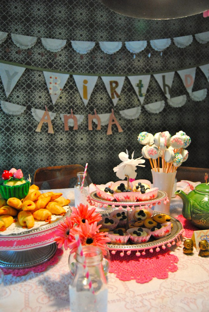 Doilies, flowers, garlands, a tea pot, ribbons and sprinkles make for a very girly table!