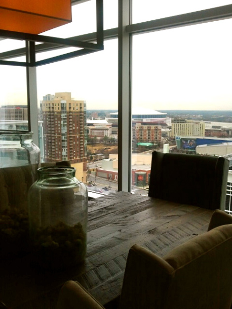 The view of downtown Atlanta from the W Hotel atop a reclaimed wood dining table and upholstered chairs.