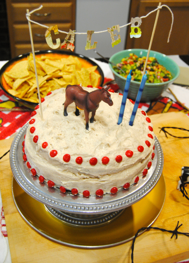Layered cake decorated with Red Hots, horse, candles and banner!