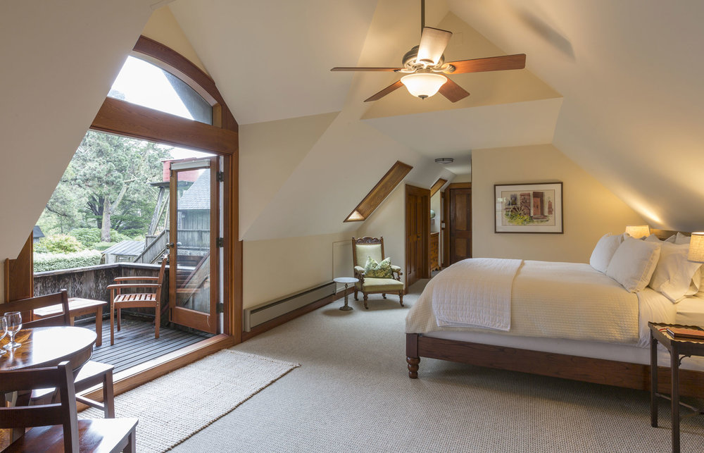 The Carriage House Grand Suite bedroom with luxurious king bed, balcony, and lots of natural light.