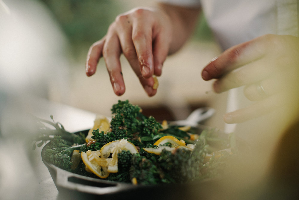 a chef's hands prepare a bowl of greens