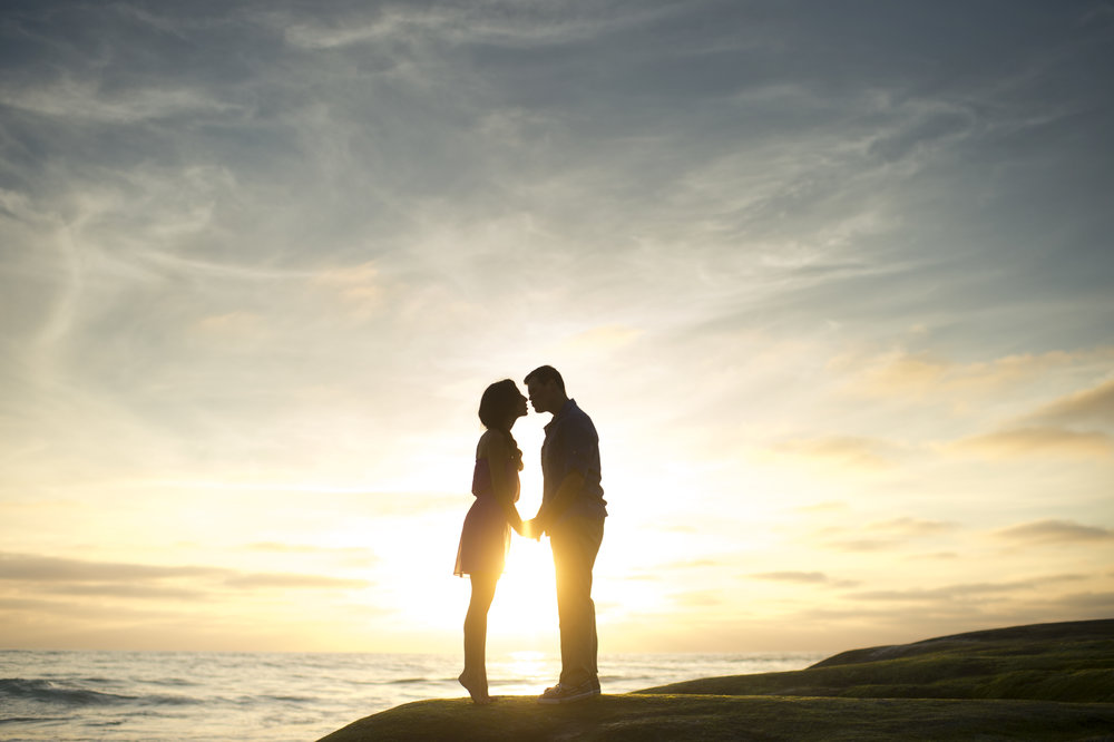 the silhouette of a couple kissing with ocean and sunset in the background