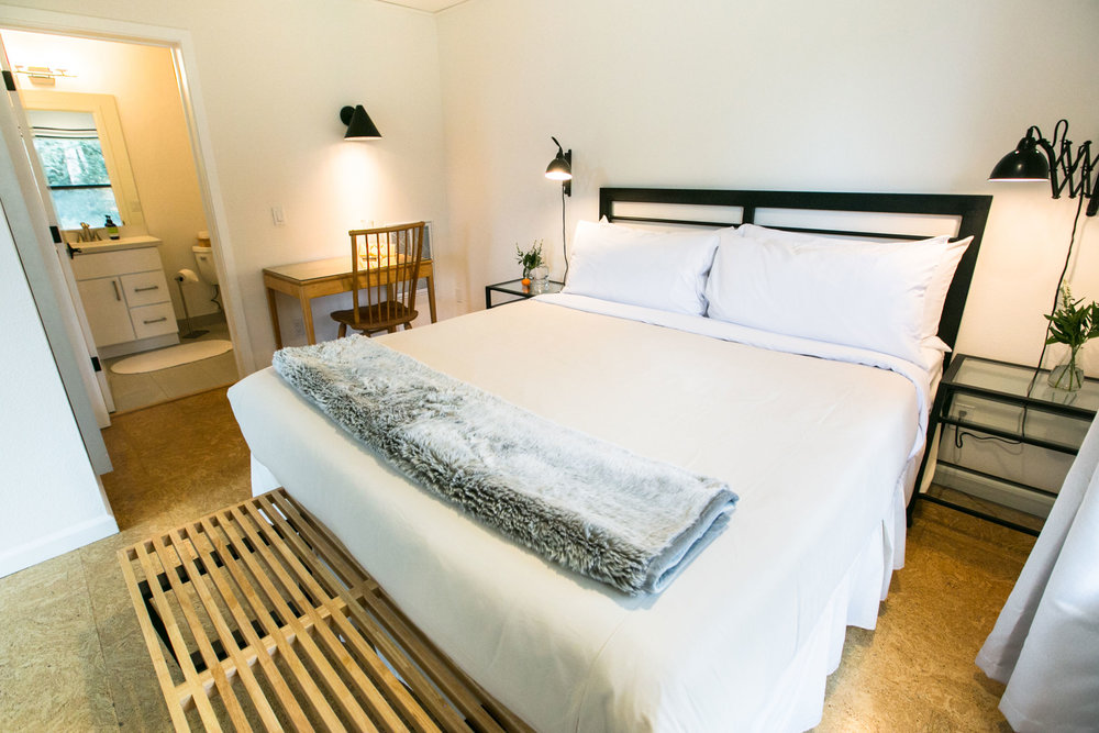 Room 201 in the Lodge with a comfy bed, plush blanket, and cork floors