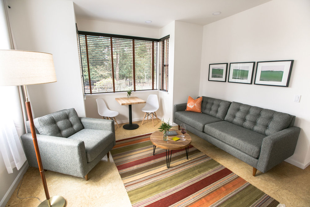 The seating area in room 101 at The Lodge has modern furnishings with sofa, chair, and table with side chairs