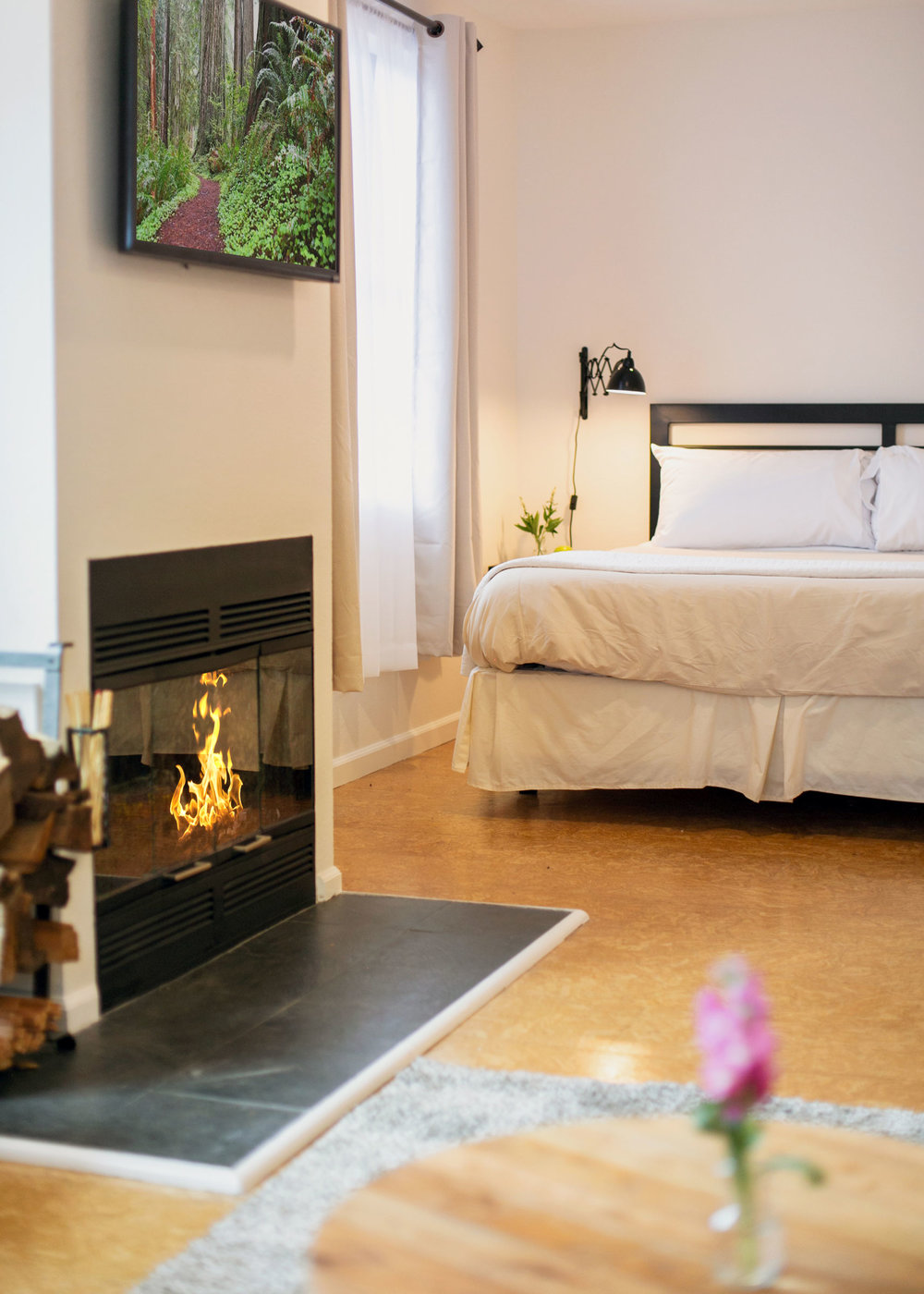 The bed and fireplace of room 102 at The Lodge at Glendeven Inn & Lodge outside of Mendocino