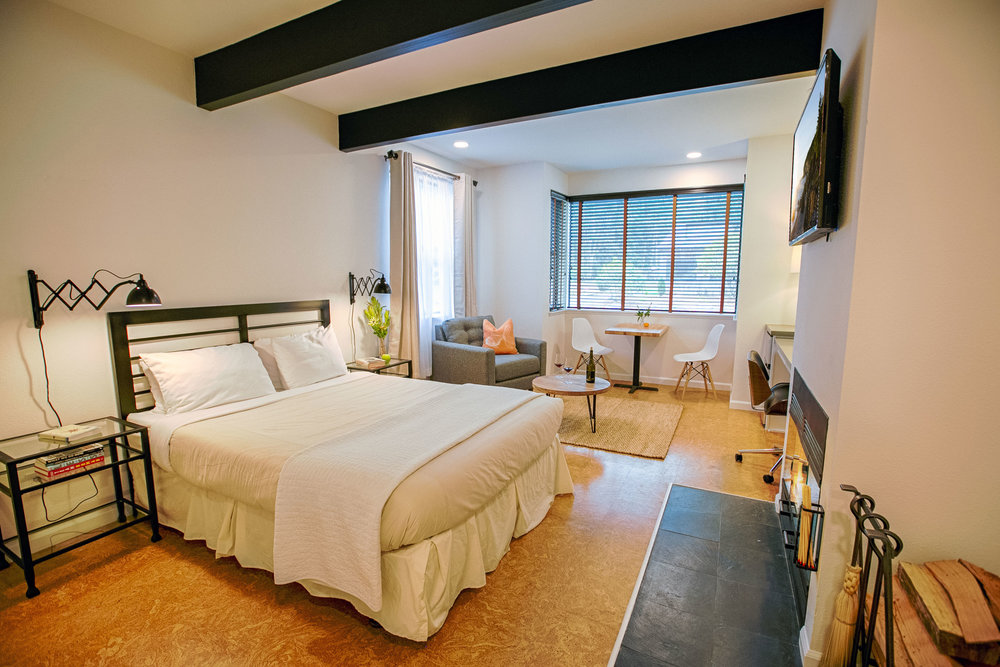 Room 104 in the Lodge with a comfy bed, wood-burning fireplace, sitting area, desk space, and cork floors