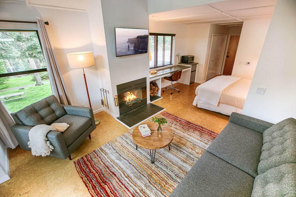 Room 206 in the Lodge at Glendeven with cozy fire in the fireplace, flat screen TV, sitting area, workspace, and queen bed.