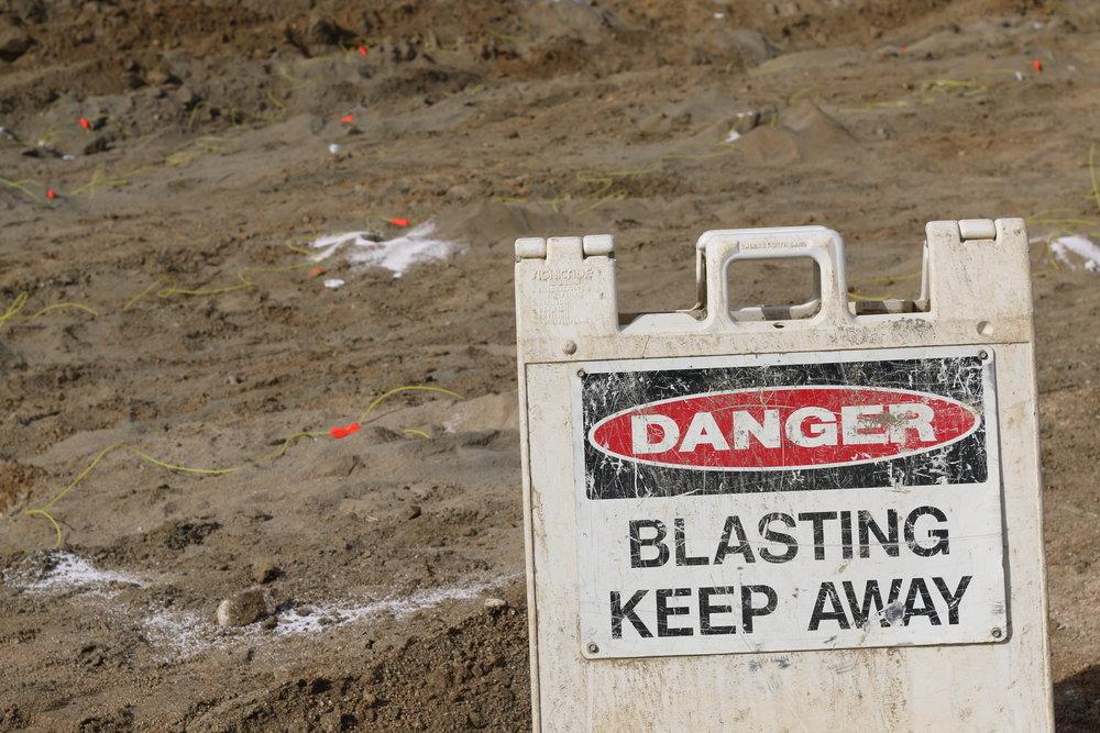 sign reading danger blasting keep away
