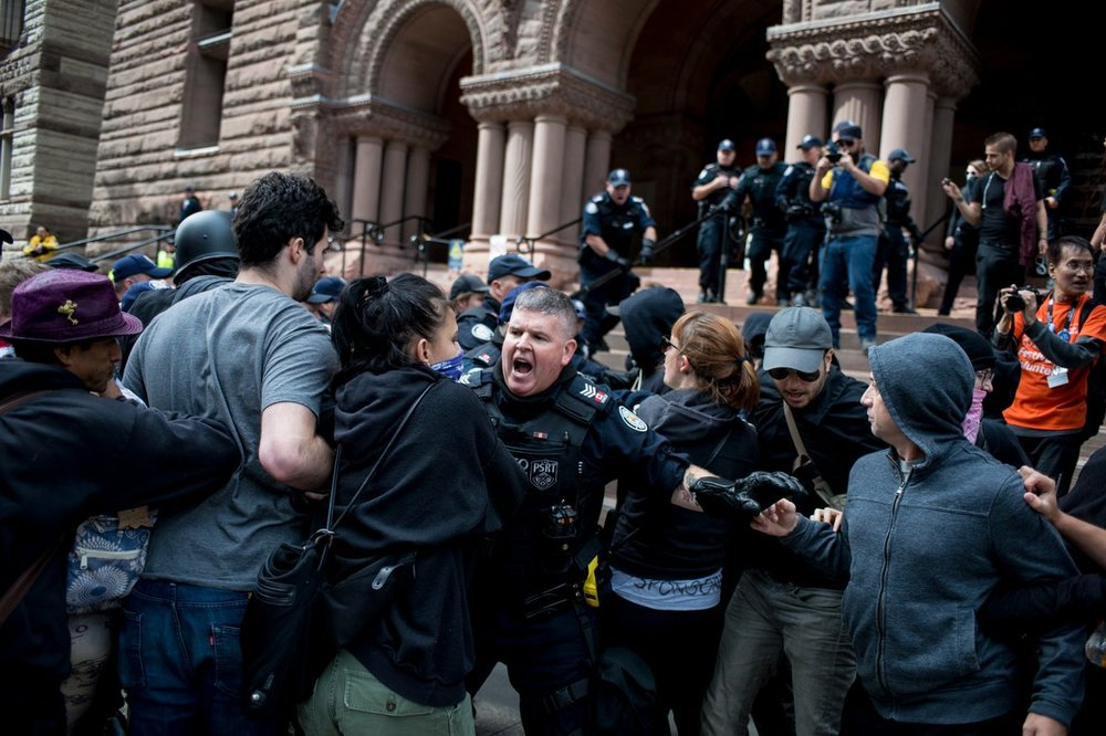 A Toronto Police Officer struggles against a line of Antifa protestors (ALI JAVEED/ THE UNDERGROUND)