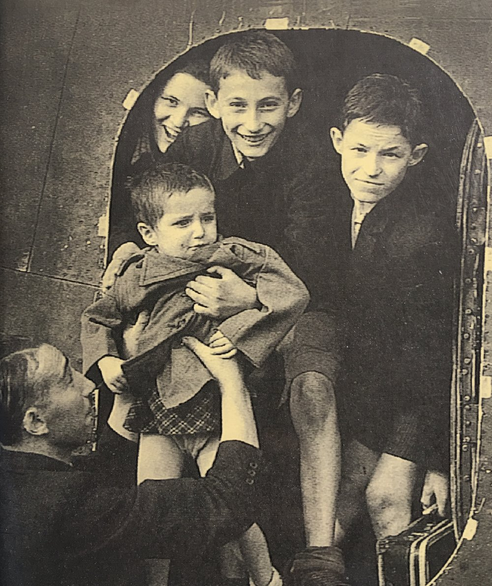 Sidney Finkel, one of the Ascot boys arriving in England in August 1945. He is holding a younger child as he gets out of the plane. Photo: Sidney Finkel.