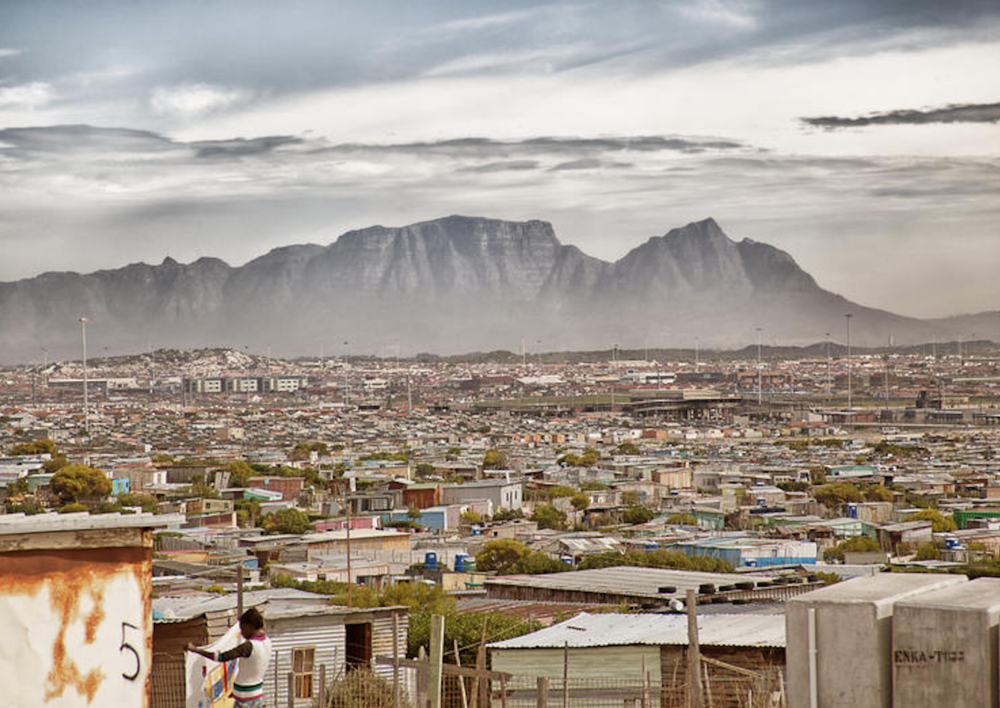 """Khayelitsha means """"our new home"""" in Xhosa, one of the official languages of the country. It is the second largest township in South Africa after Soweto. Table Mountain in the background."""