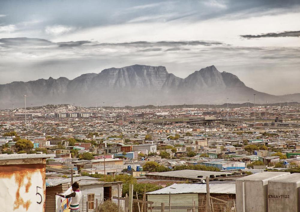 """Khayelitsha signifie """"notre nouvelle maison"""" en Xhosa, l'une des langues officielles du pays. C'est le deuxième plus grand township d'Afrique du Sud après Soweto. Table Mountain dans le fond."""