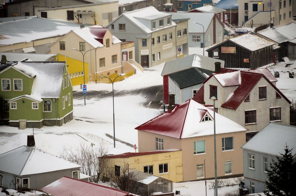 Shot from above of a series of colorful snow covered houses in Holmvik in Icelands Westfjords