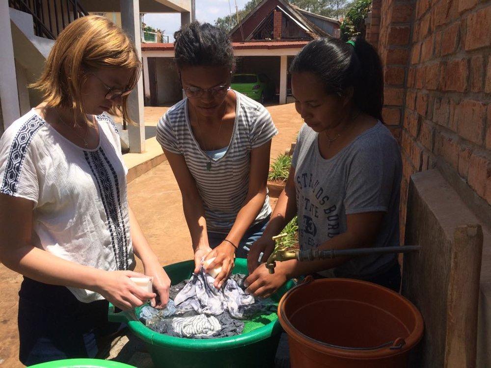 Tiffany og Sylvi lærer Johanna å vaske klær.