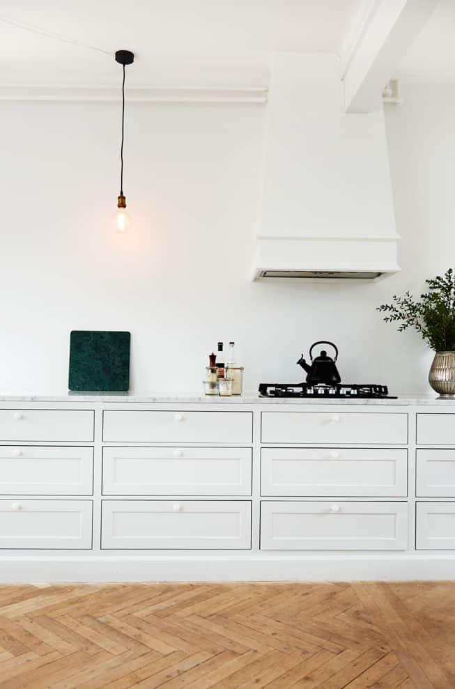Hvidt snedker køkken med skuffer og emhætte