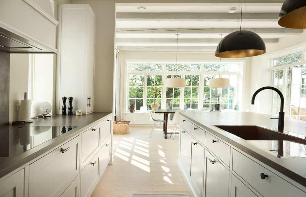 Hvidt håndlavet køkken med induktion, emhætte og håndvask