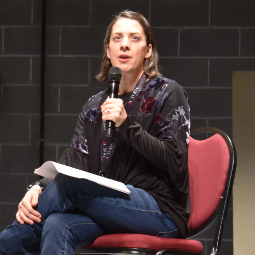 Image description: Talleri A. McRae sits on stage in a read chair talking to an audience holding a hand held microphone up to her mouth. Behind her is a concrete brick wall. She is wearing blue jeans and a black blouse with an embroidered floral print.