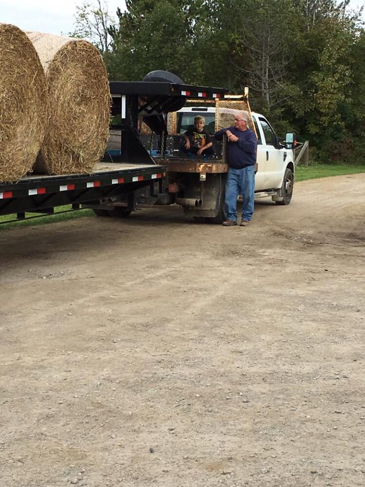Man leans on hay delivery truck talking to child
