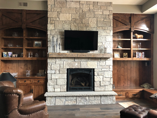 The beam was modified to fit above the stone fireplace between beautiful custom built cabinetry.