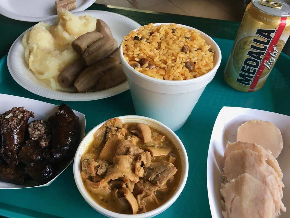 A typical spread of fixings from a lechonera. From left to right: stewed yuca, boiled guineo (green banana), arroz con gandules, a cold Medalla, yautia (taro root), cuajito (stewed pig stomach), and morcilla (fried blood sausage).