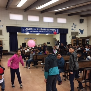Students playing by bouncing balloons with heads