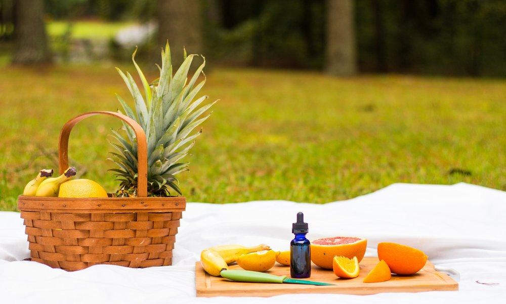 Peninsula Holistics CBD Oil on picnic blanket with fruit