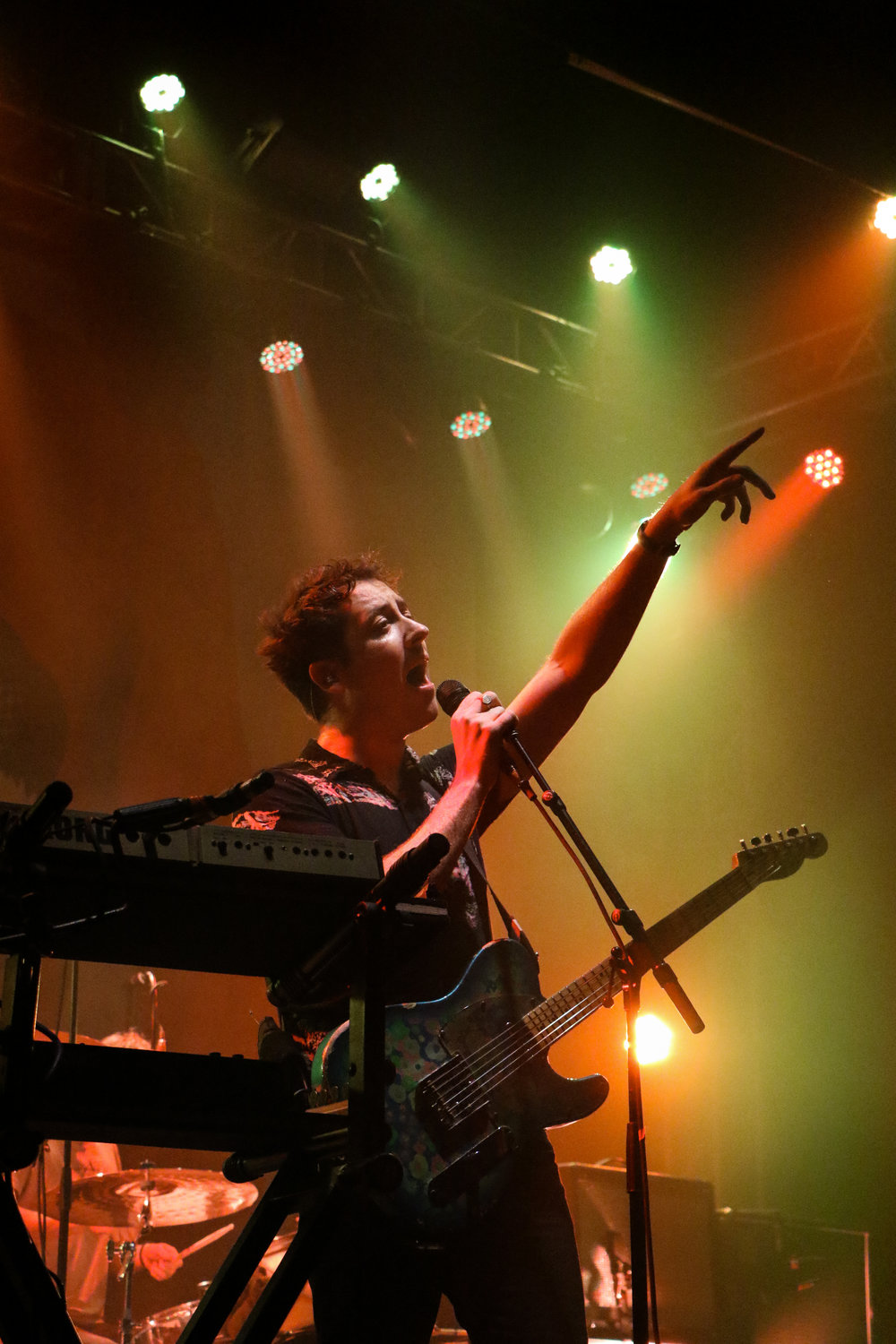 Lead singer, Matthew Murphy's silhouette stands out against the colorful stage lights.
