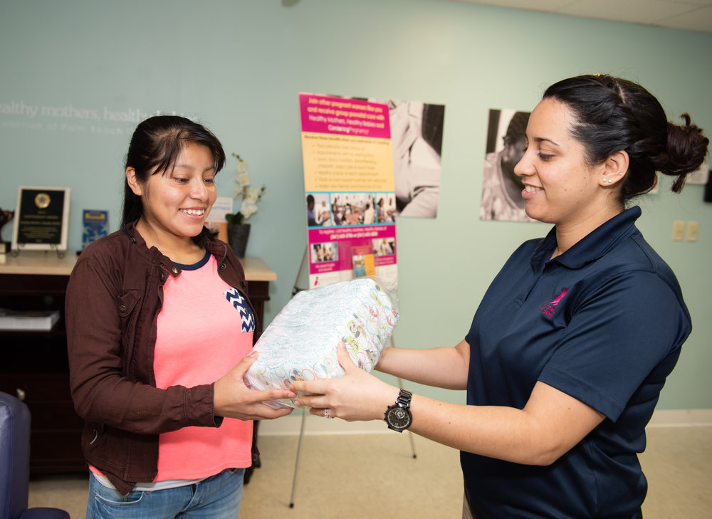 Mother receiving baby supplies for family.