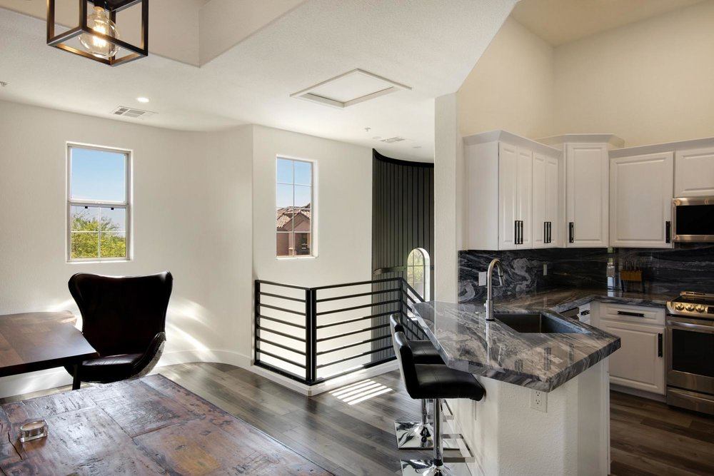 Kitchen with white cabinets and black bar stool