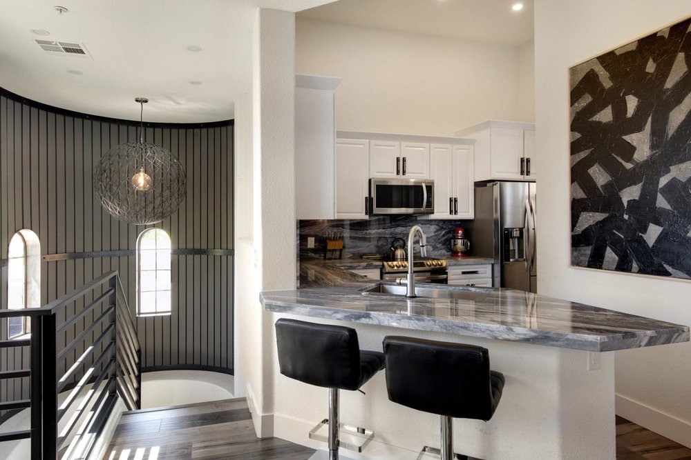Kitchen with granite countertop sink and two black bar stool