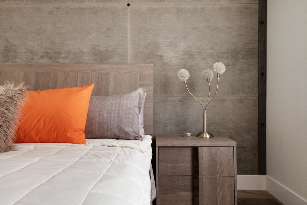 Bedroom with stylish lamp on wooden bedside table