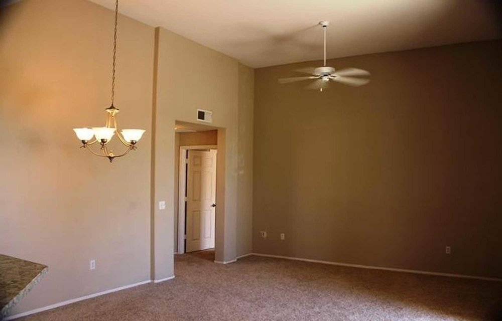 Dark painted room with ceiling fan and hanging light