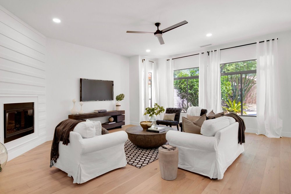 Modern living room with white sofa set and large windows