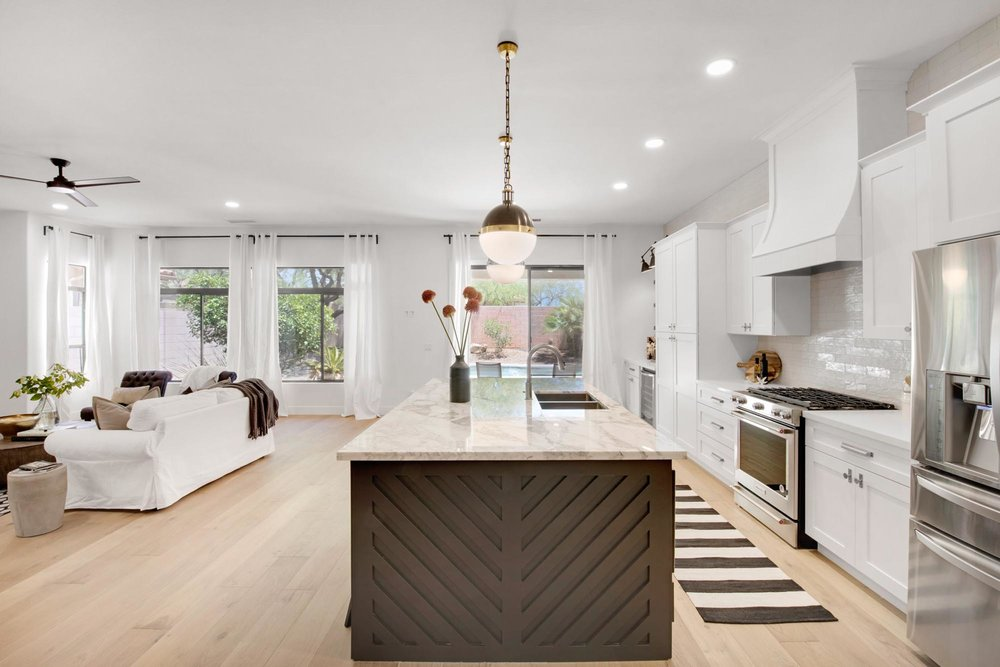 Kitchen island with flowers in vase on granite countertop