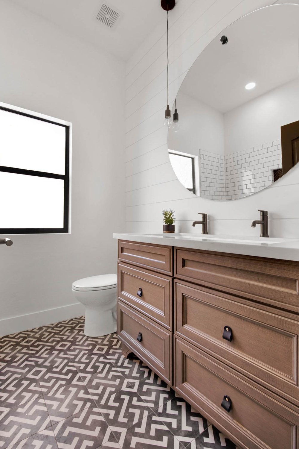 Toilet room with sink and stylish mirror