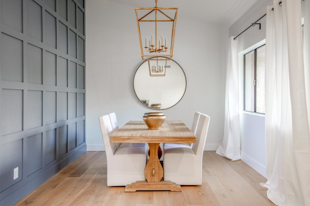 Wooden table with four white cushion chairs mirror and hanging lights
