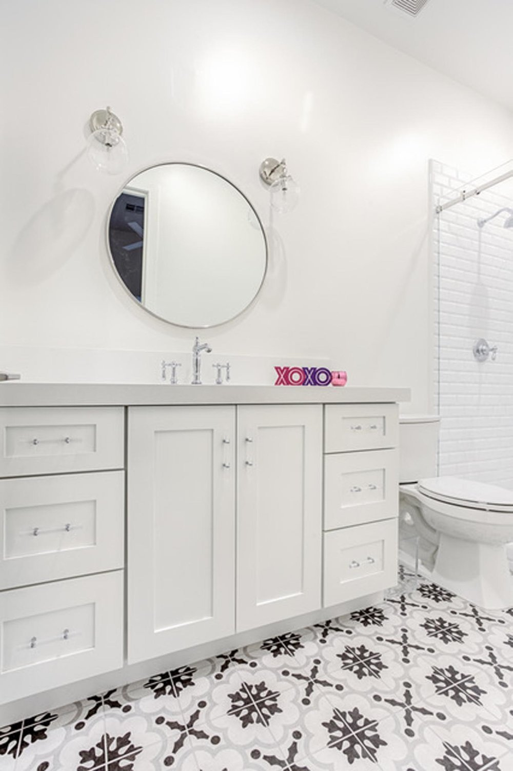 Bathroom with white sink and and round mirror